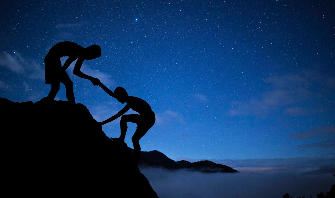 Millennial shadows helping each other climb up a mountain during a blue starlit twilight sky