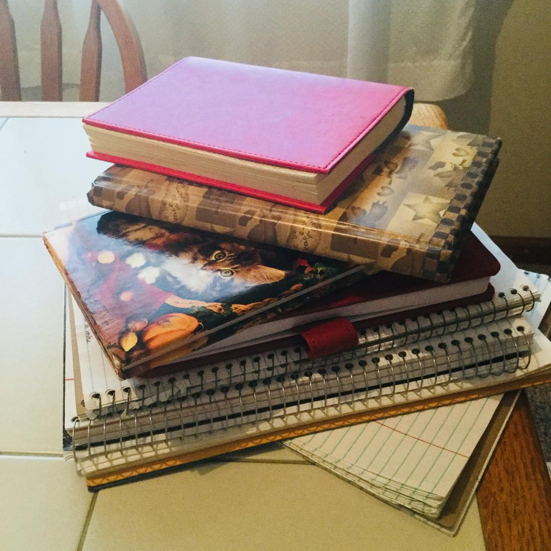 Stack of Gold Millennial writer's notebooks and spirals