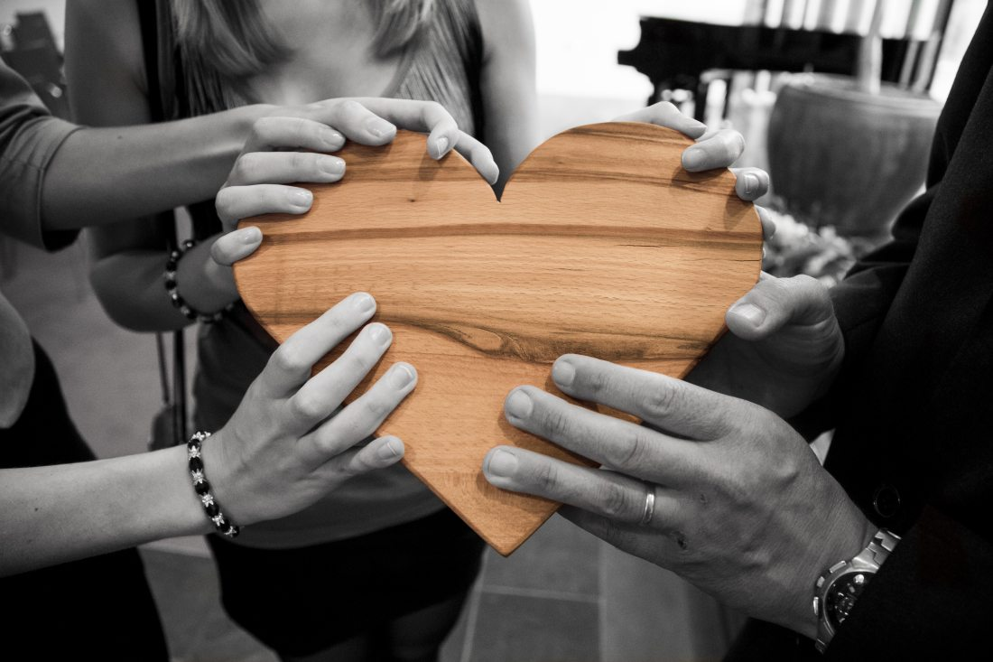 Group of millennials holding a wooden heart together