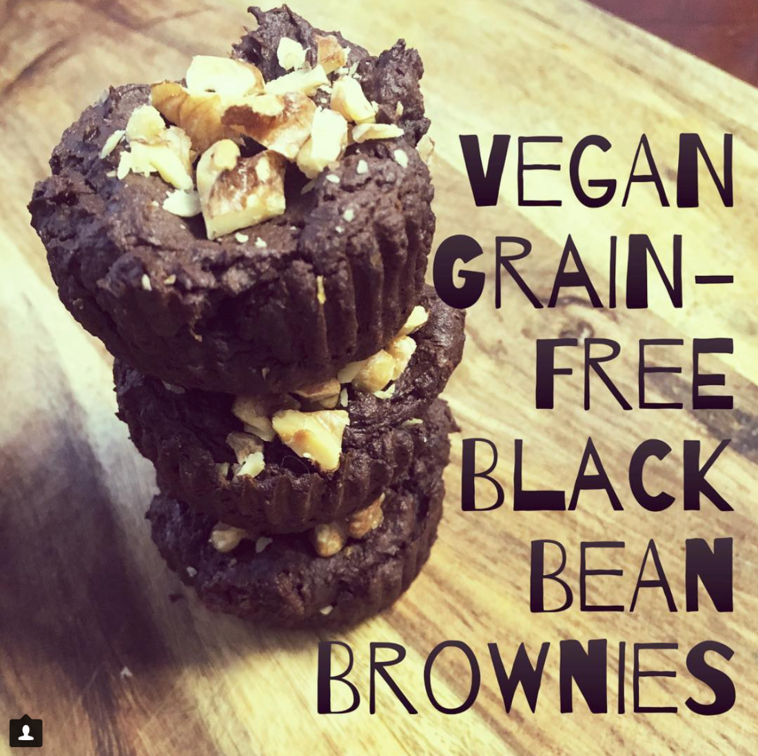 Gorgeous food photography of vegan grain free black bean brownies with chopped walnuts stacked on a cutting board