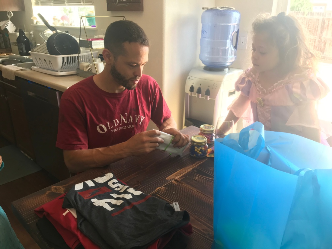 a man opens presents on Father's Day while his daughter watches