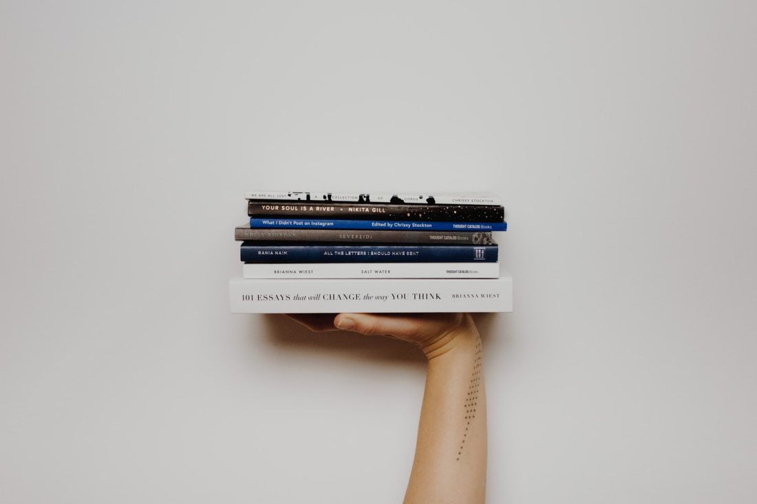 person's arm and hand holding a pile of books