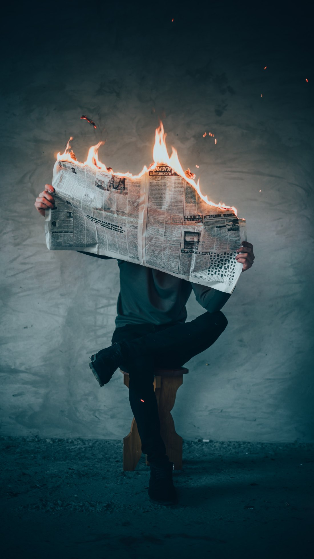 A man sits on a stool holding a burning newspaper