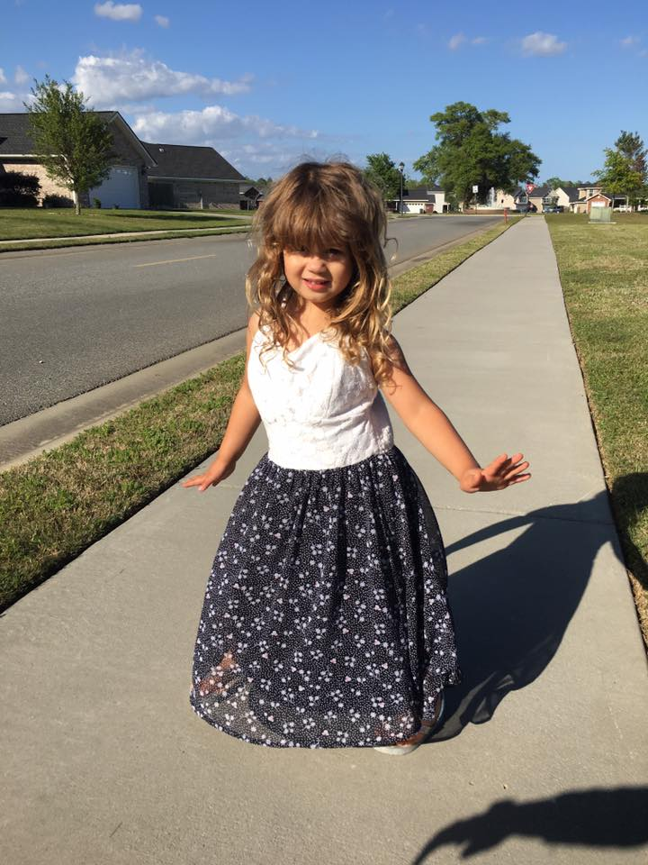 little girl posing in her mother's dress on the sidewalk