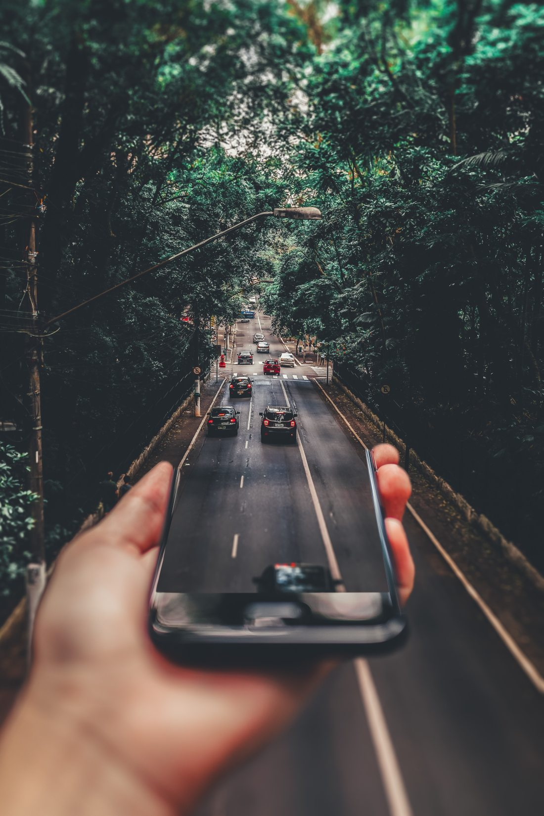 a hand holding a smart phone turns into a road with cars