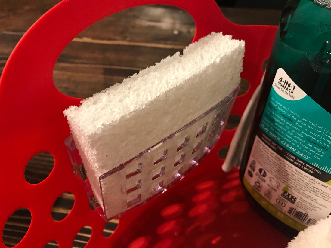 a white sponge in a sponge holder attached to a plastic basket
