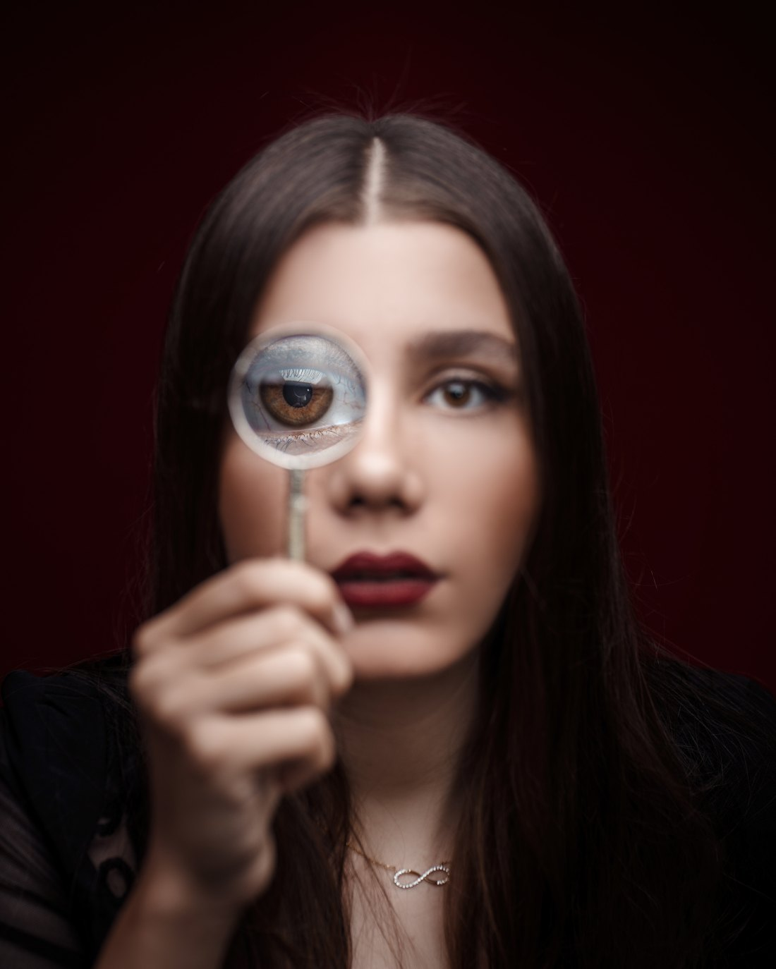 A woman holds a magnifying glass up to her eye
