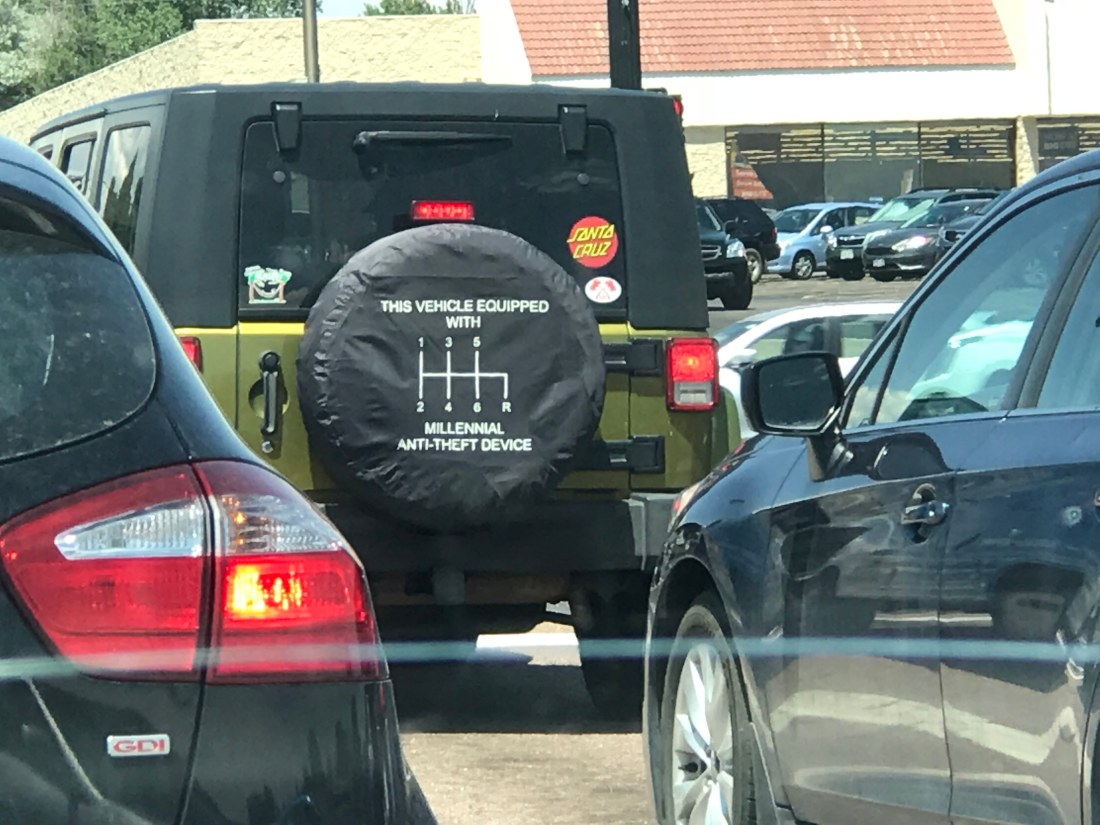 "A tire cover on the back of a Jeep reads ""This vehicle equipped with millennial anti-theft device"""