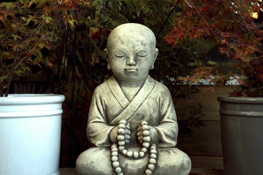 a buddha statue sits praying peacefully, meditating