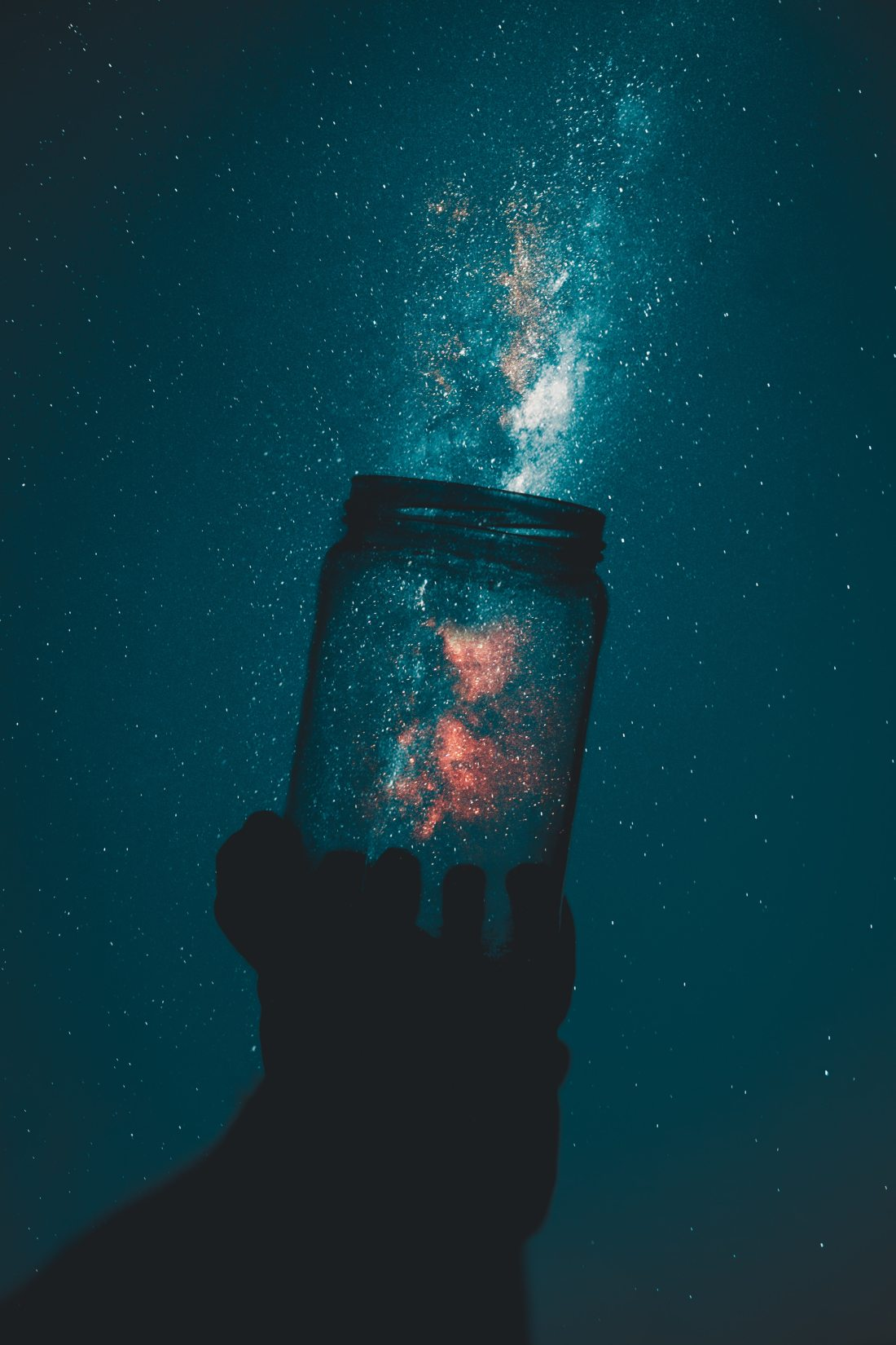 a cosmic cluster of stars in the night sky emerges from a glass jar