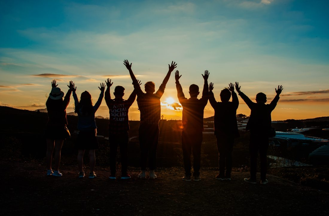 Group of millennials at sunset arms raised to the sky