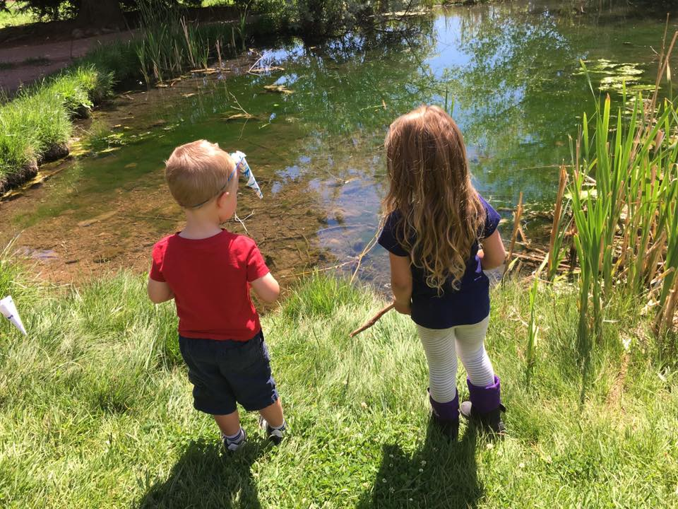 two beautiful children stand before a pond in the sunshine