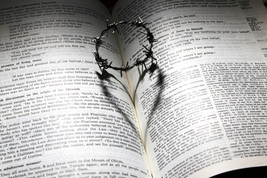 Bible, crown of thorns in the open pages, heart shadow