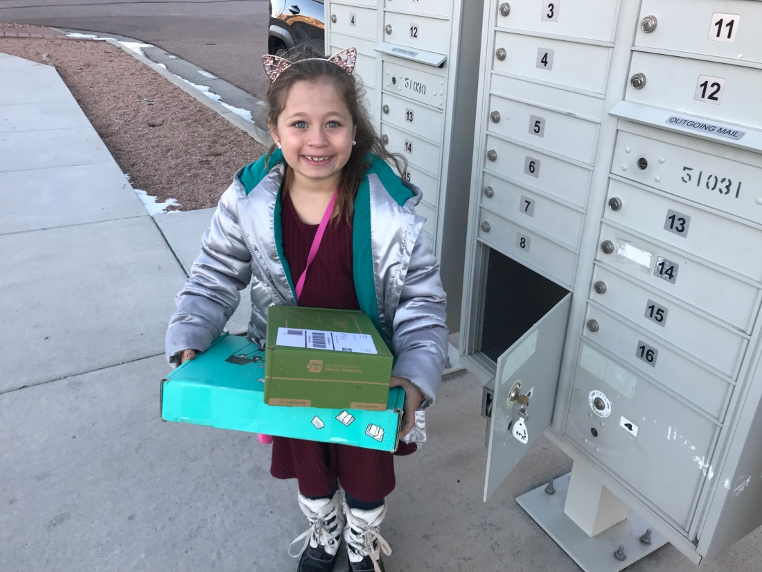 little girl standing next to mailbox with packages