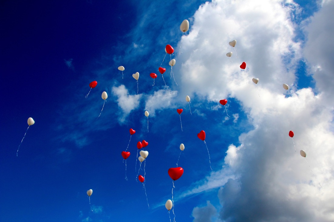 Blue sky and clouds with red and white heart balloons floating