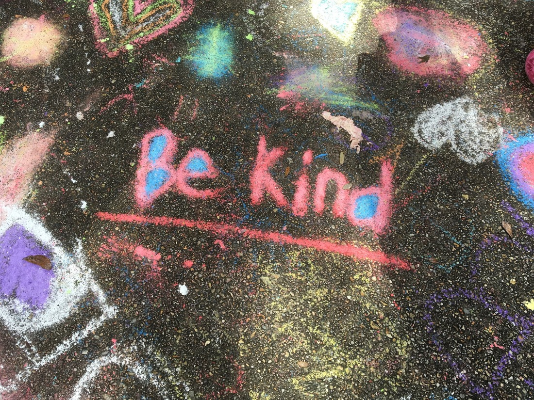 "Colorful chalk art on blacktop saying ""be Kind"""