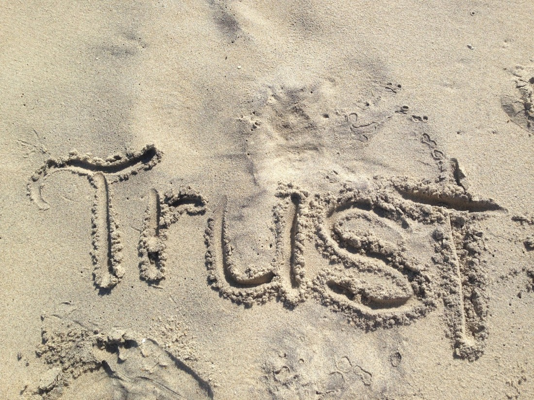 The word trust written in sand
